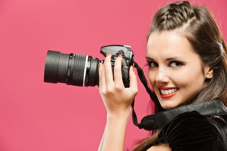 photographers: Young beautiful smiling woman-photographer hold in hands DSLR, going to make picture, on red background. Stock Photo