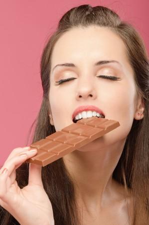 chocolate melt: Bella giovane donna ha chiuso gli occhi e morsi da mattoni di cioccolato, su sfondo rosso. Archivio Fotografico