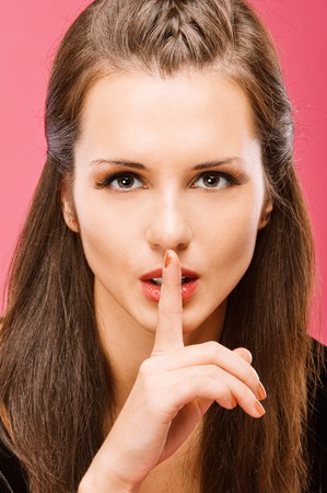 Young beautiful brunette calls for silence, having brought to mouth index пале, on red background. photo