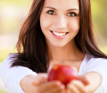eating out: Smiling young woman stretches red apple