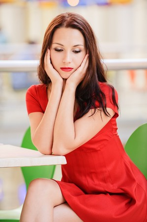 Young beautiful dark-haired woman in red dress sits at little table in small cafe and thinks of unfortunate life. photo