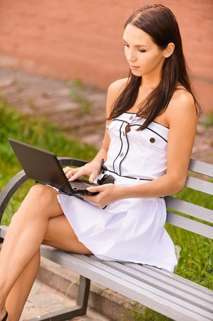 Young beautiful brunette student sits on bench about university and works behind black laptop. photo