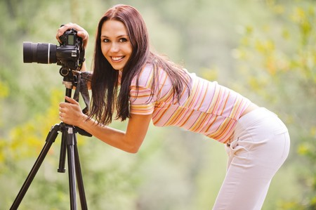 slr: Beautiful smiling girl with camera on nature.