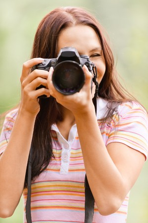 shootting: Beautiful smiling girl with camera on nature.