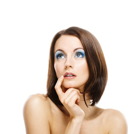 bared: Charming young woman with bared shoulders has brought forefinger to mouth and looks up, reflecting on the life. Stock Photo