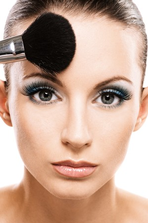blush: Charming young woman applying blusher close up. Stock Photo