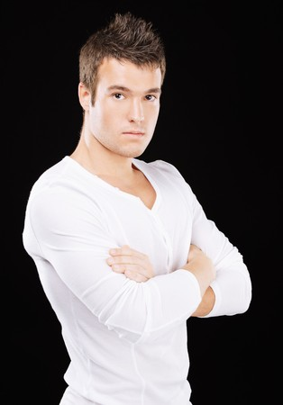 Portrait of courageous young man with crossed hands in white clothes, on black background.