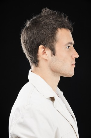 Portrait of beautiful young man in white suit in profile, on black background. Stock Photo - 8247679
