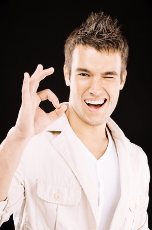 Beautiful young man shows sign OK and winks, on black background. Stock Photo - 8247680