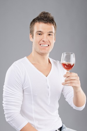 tells: Beautiful laughing young man pick up a wineglass and tells toast, on gray background. Stock Photo