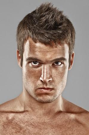 gaze: Ernstige jonge man lours, op een grijze achtergrond.