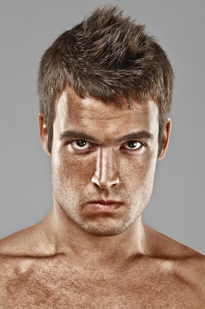 gaze: Severe young man lours, on gray background. Stock Photo