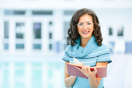 Beautiful smiling dark-haired woman in blue sweater and glasses reads interesting red book against spacious hall. photo