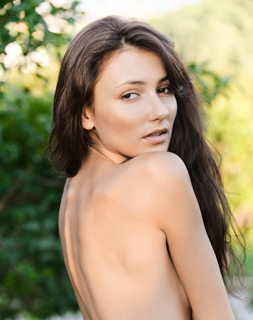 Portrait of back charming woman with naked shoulders, against green foliage. photo