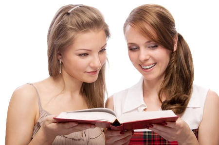 Two young beautiful  women  reading  a book isolated on white background photo