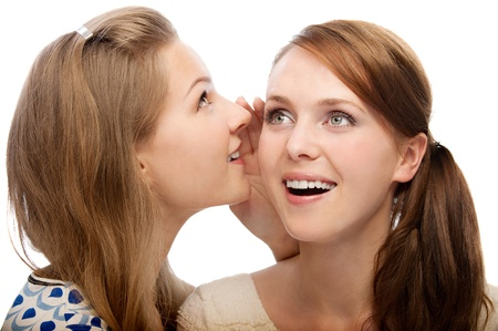 Two young beautiful  women  secret in isolation on a white background photo