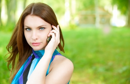 Young beautiful woman talks by mobile phone, on green background.  photo