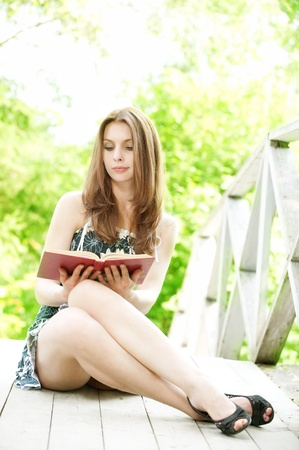 beautiful young woman  reading  a book on green background photo