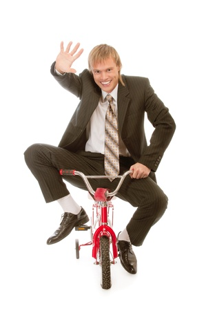 goes: Businessman goes on childrens bicycle, isolated on white background.