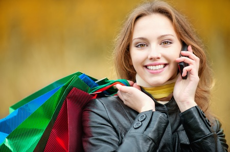 Young smiling woman with shopping talking on a mobile phone photo