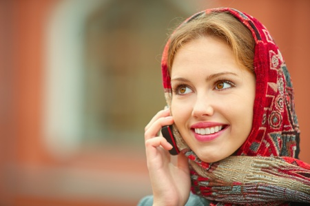 Young beautiful smiling woman in a red kerchief was talking on his cell phone Stock fotó