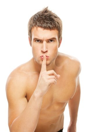 Young muscular guy calls for silence, raising his forefinger to his lips, white background. Stock Photo - 9286103