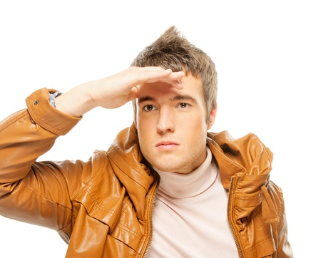 put forward: portrait of a beautiful young man in a leather jacket, put his hand to his forehead and looks forward, isolated on a white background. Stock Photo