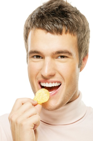 A handsome young man in a sweater eating chips isolated on a white background photo