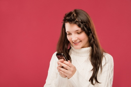 A beautiful young girl in a white sweater reads SMS from your mobile phone on a red background Stock Photo - 9286151