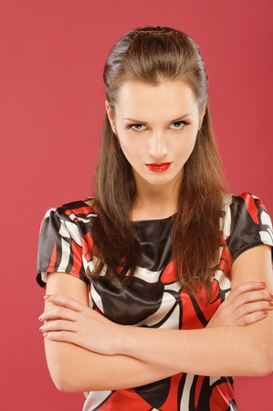 Portrait of a beautiful serious brunette on a red background photo