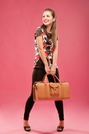 leather bag: Young beautiful dark-haired girl standing with a large brown leather bag, on a red background