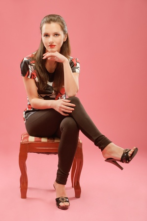 beautiful girl sitting on a chair with his legs crossed on a red background. photo