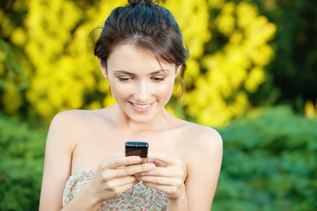 Beautiful young woman to read SMS from your mobile phone on natural background Stock Photo - 9286080