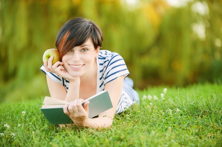 A beautiful young girl with an apple lying on the grass and reading a book on a background of green nature