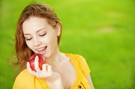 Portrait of a young beautiful girl with red apple on a background of green nature photo