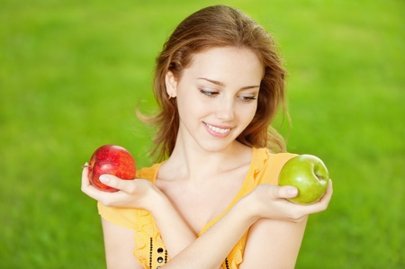 Portrait of a young beautiful girl with red and green apples on a background of green nature photo