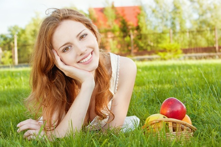 A beautiful young girl lying on the grass beside a basket of fruit is, on a background of green nature photo