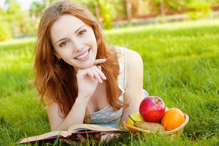 A beautiful young girl lying on the grass and reading a book beside a basket of fruit is, on a background of green nature
