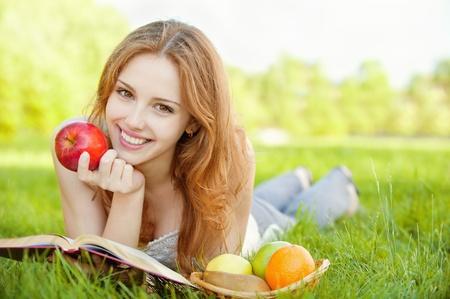 frutas divertidas: Es una hermosa joven con una manzana tirado en el pasto y leyendo un libro junto a un cesto de frutas, sobre un fondo de naturaleza verde