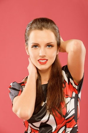 Portrait of a beautiful brunette on a red background photo