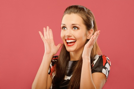 Young beautiful woman delightfully plants hands and is surprised, on red background. photo