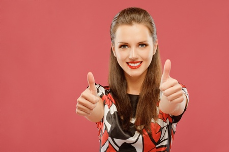 Beautiful young woman lifts thumbs upwards as sign of OK, on red background. photo
