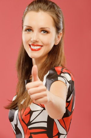 Beautiful young woman lifts thumb upwards as sign of OK, on red background. photo