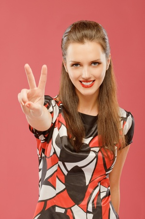 Beautiful young woman lifts two fingers the letter V in victories, on red background. photo