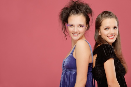 Two beautiful young girls smile and stand backs to each other, on red background photo