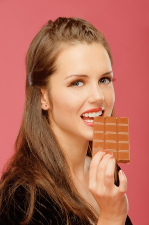 Beautiful young woman has closed eyes and bites off from chocolate brick, on red background. photo