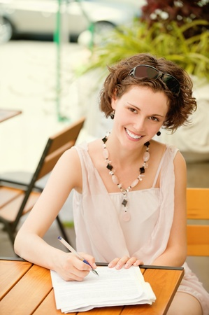 outside portrait of beautiful curly young woman sitting at the park cafe table and white pen in writing-book photo
