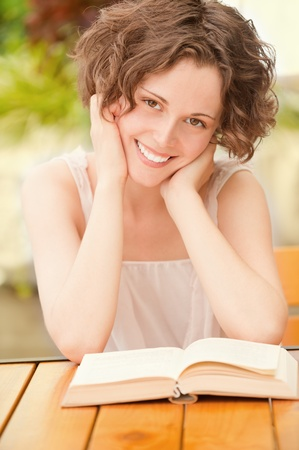 outside portrait of beautiful curly young woman sitting at the park cafe table and reading book photo