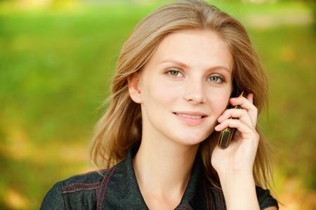 conversa: Beautiful sonriente conversaciones de ni�a en telefon�a celular, contra el c�sped verde de verano. Foto de archivo