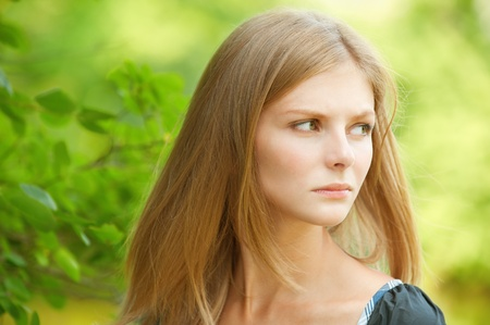 reflects: Young woman has inclined head and reflects.